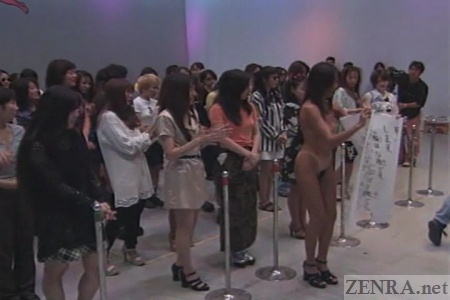 Single nudist Japanese female amongst clothed crowd