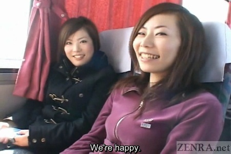 Two happy Japanese women sit in a bus