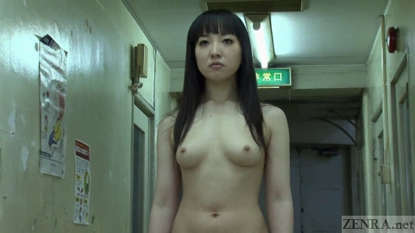 Nude woman walks down hospital hallway