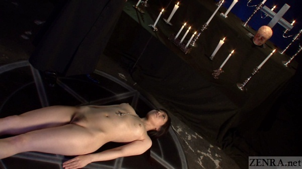 Nude Japanese woman rests near candles