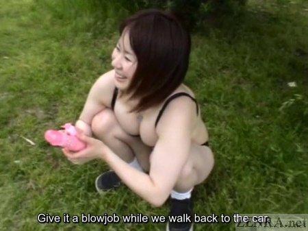 Japanese woman in black lingerie squats in park