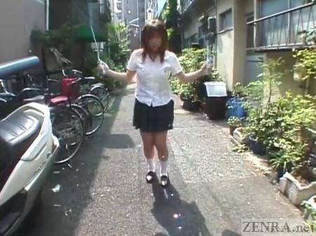 Japanese schoolgirl jump ropes outside