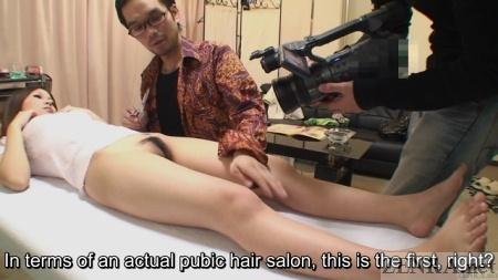 asian hairdresser shaves man