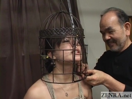Japanese woman has head put in bird cage