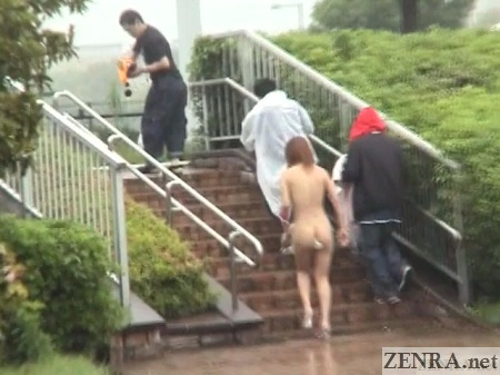 Naked Japanese woman outside climbs chair