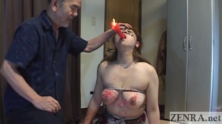 japanese woman holds candle in mouth