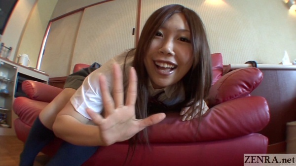 chirpy japanese schoolgirl waves to camera