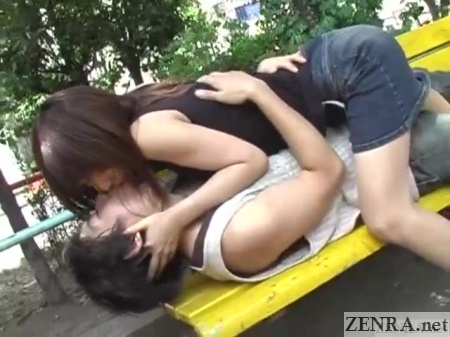 embracing and kissing japanese couple in public park