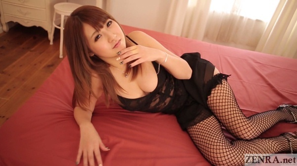 kitagawa hitomi in fishnet stockings lounges on bed