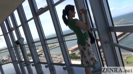 japanese woman takes picture of ocean scenery