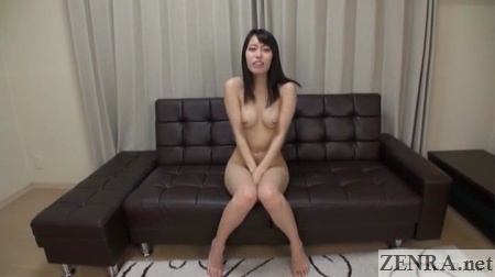 naked japanese woman sits on leather sofa