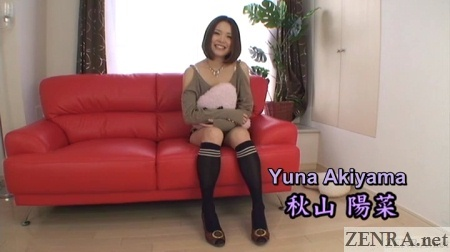 yuna akiyama sits on red leather sofa