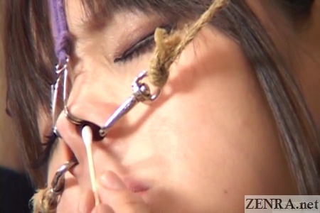 cotton swab up nostril of japanese maid