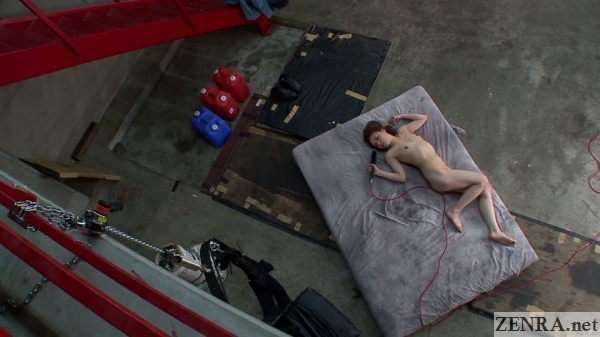 overhead view naked japanese reporter on mattress in factory