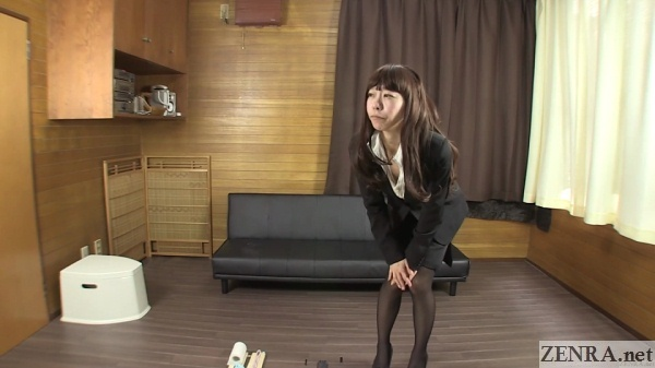 older japanese office lady bent over holding in pee