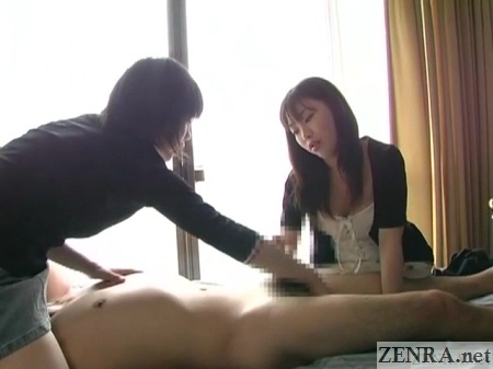 two japanese woman give handjob to naked man