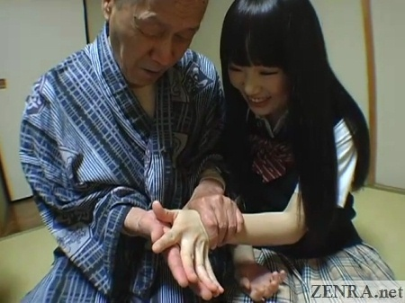 pale schoolgirl matches hands with old man