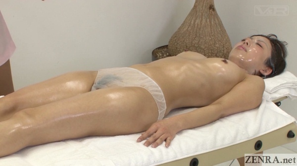 supine topless female customer receiving semen facial masque