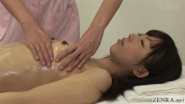female japanese customer receives oil breast massage