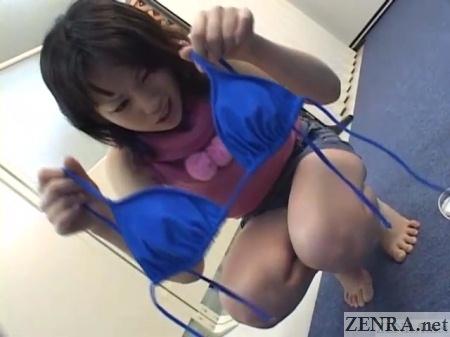 jav idol hopeful holds up blue bikini top